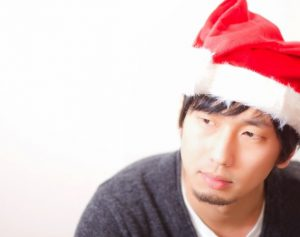 サンタの帽子をかぶって寂しそうな人