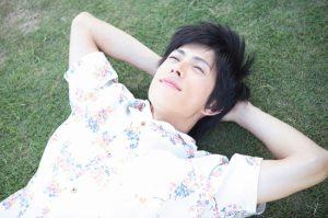 芝生に寝転がる男性