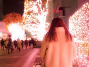 イルミネーションの中を歩く女性