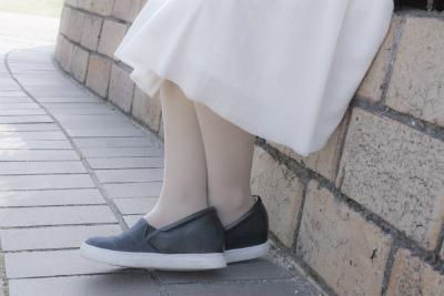 スリッポンを履いた白い服の女性